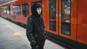Poika seisoo metrolaiturilla metron edessä.