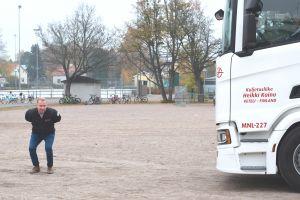 Man som står nedböjd framför en vit lastbil på en grusplan.
