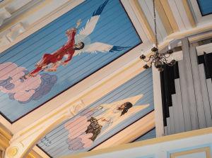 Kaksi kirkasväristä enkeliä maalattuna kirkon kattoon, yksi kiinalaisen naisen näköiseksi, toinen romaninaisen näköiseksi.