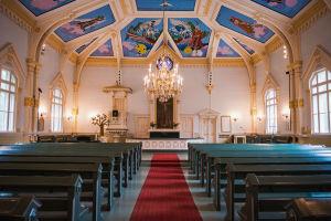 Laaja sisäkuva kirkosta ovelta kohti alttaria, sisäkaton kirkkaat kuvat näkyvät, keskellä kattokruunu
