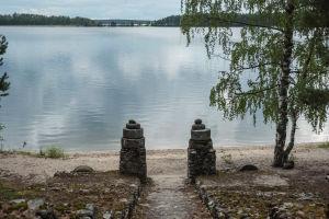Två stenstolpar, i bakgrunden en sandstrand och en sjö.
