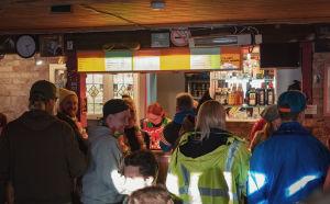 Ihmisiä baaritiskillä jonottamassa juomia, baari rakennettu vanhaan navettaan, tiiliseinää taustalla.