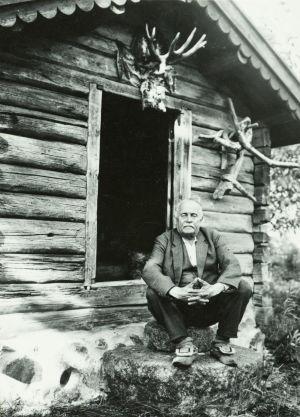 Gammal, svartvit bild på äldre kostymklädd man som sitter på stentrappa framför en bod. På väggen ovanför dörröppningen älghorn och på väggen stora, krokiga grenar.