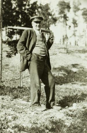 Gammal, svartvit bild på äldre man i kostym ute i naturen.