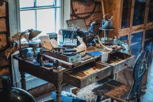 Överbelamrat, slitet arbetsbord med verktyg och reservdelar för att tillverka uppstoppade djur.