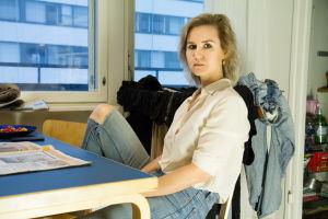 Sisko Savonlahti istuu rennosti keittiönpöytänsä äärellä tavaroidensa ympäröimänä.