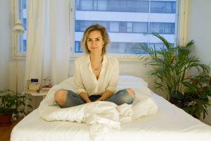 Sisko Savonlahti istuu risti-istunnassa sängyllään.