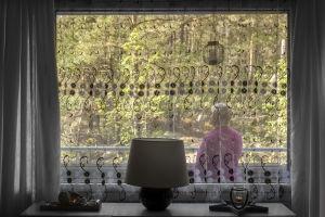 Sari Palmunen seisoo parvekkeellaan ja katsoo ulos luontoon.