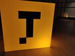 Nya serviceapplikationen Taksini:s logo: en gul kub med ett svart, stiliserat T.