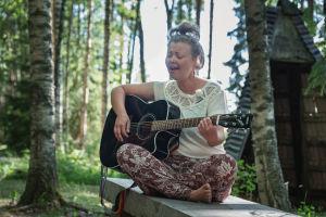 Muusikko Heidi Niinimäki soittaa kitaraa Alpo Jaakolan patsaspuistossa, ympärillä vihreää metsää.
