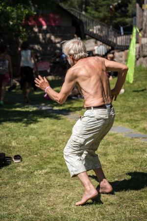 Selin kuvattu iäkäs mies ilman paitaa tanssimassa Natural High Healing Festivaalilla.