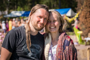 Kaksi ihmistä, mies ja nainen, nojaavat päätään toisiaan vasten ja katsovat kameraan ja hymyilevät Natural High Healing Festivaalilla.
