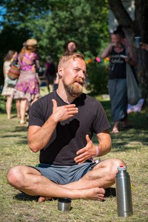 Mies istuu nurmikolla jalat ristissä, selittää käsillä