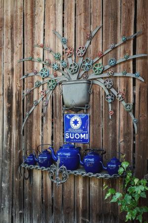 Raudasta ja vanhoista kahvipannuista tehty teos ladon seinässä Matti Järvenpään Rautapuistossa.
