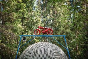Punaiseksi maalattu moottoripyörä suuren, pyöreän häkin päällä Matti Järvenpään Rautapuistossa.