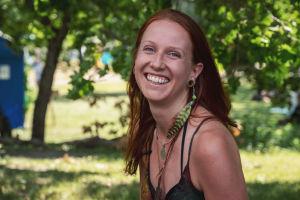 Punahiuksinen Ila Lassfolk hymyilee kameralle, taustalla vihreää puistoa, Natural High Healing Festivalilla