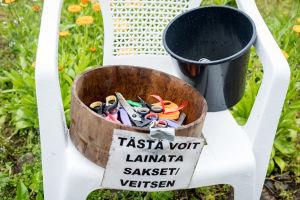 Muovituoli jossa on saksia ja veitsiä, joita kukkien poimijat voivat lainata.