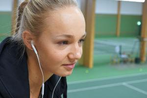 Tennispelaaja Oona Orpana keskittyy peliin kuunnelleen musiikkia.