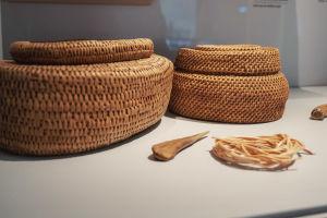 Två runda, flätade korgar med lock, ett vasst föremål av ben, en repsnodd av lin.