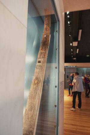 En med från en släde i vitrinskåp, i bakgrunden människor som går omkring i ett museum.