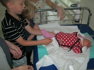 Haapalaisten perhe sairaalassa. Isoveli laittaa Liinulle sukkaa jalkaan.