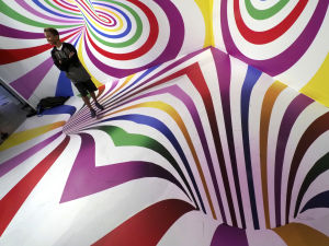 Man står i färgglad optisk illusion på Candytopia.