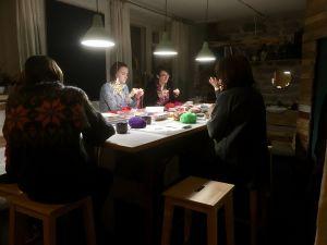 Damer sitter runt ett bord och stickar