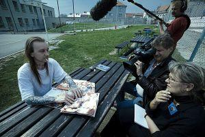 Helena Třeštíkován dokumentin René päähenkilö istuu vankilan pihalla ja dokumentin kuvaus on käynnissä.