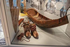 Pälsstövlar, färggrant band och liten träbåt i vitrin.