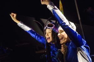 Aino-Kaisa Saarinen ja siskonsa iloitsevat hiihtokilpailussa saamastaan voitosta. Hiihtoasuiset naiset seisovat rintarinnan, kädet pystyssä. Rooleissa Sanna-June Hyde ja Vappu Nalbantoglu.