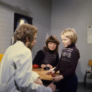 Timo Antero (Kyösti Väntänen) lääkärintarkastuksessa. Vieressä lääkäri (Esa Pakarinen Jr) ja opettaja (Pirkkoliisa Tikka). 1977.