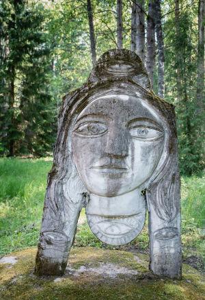 Harmaa patsas, jossa kasvot, taustalla koivikkoa