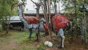 Kaksi suurta, jätemateriaaleista tehtyä norsulintu-veistosta.