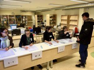 Valförrättarna sitter på rad och väntar på att få hjälpa väljare som har kommit för att rösta till Muraste skola en bit utanför Tallinn.