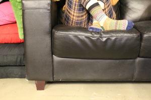 ihminen istuu nahkasohvassa jalat ristissä