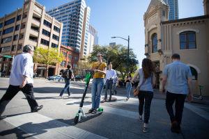 Fotgängare och en person med elektrisk sparkcykel som korsar en gata i Austin i Texas.