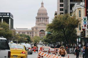 En del av staden Austin i Texas fotograferad i gatunivå. I bakgrunden en stor byggnad med pelare, kupoler och spira.