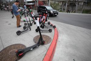 En ung man står på en trottoar där många elektriska sparkcyklar står parkerade. Bilden är tagen i Austin i Texas.