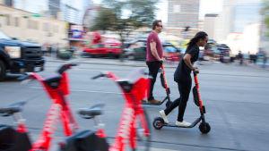 En man och en kvinna i Austin i Texas åker sparkcykel i riktning högerut på bilden.