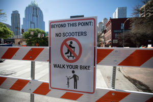Staket med en varningsskylt för personer på sparkcykel och cyklister.