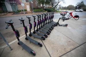 Parkerade elektriska sparkcyklar på en trottoar i Austin i Texas.