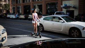 Kvinna på sparkcykel på en gata i Austin.