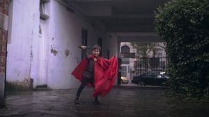 Aatos leikkii Thor-jumalaa punaisessa viitassaan, Reetta Huhtasen dokumenttielokuvassa Aatos ja Amine.