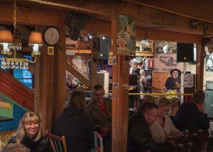 Aslak and the Eskimos -baarin sisätila, hämyisää, hymyileviä ihmisiä, taustalla soittamassa kitaristi Aslak Christiansson ja rumpali Arto Tyrni