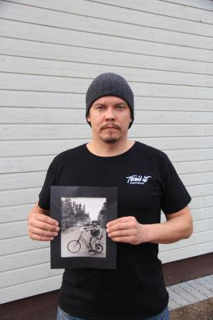 Juhana Koivisto pitää käsissään kuvaa itsestään lapsena