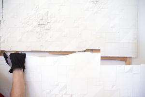 Käsi pitää kiinni Rut Brykin taideteoksen reunasta.
