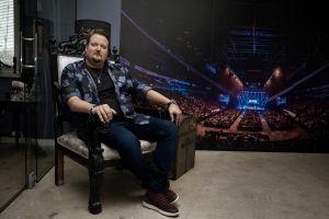 Sami Hedberg istuu isossa nojatuolissa taustallaan kuva areenakeikaltaan.