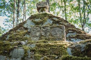 Ansikten ingraverade i sten ovanpå en mossbelupen sten.