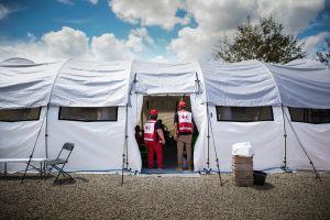 Avustustyöntekijöitä valkoisen teltan suuaukolla.