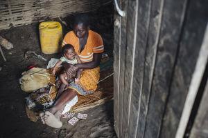 Äiti ja pitää sylissään vauvaa ja istuu savimajan lattialla.